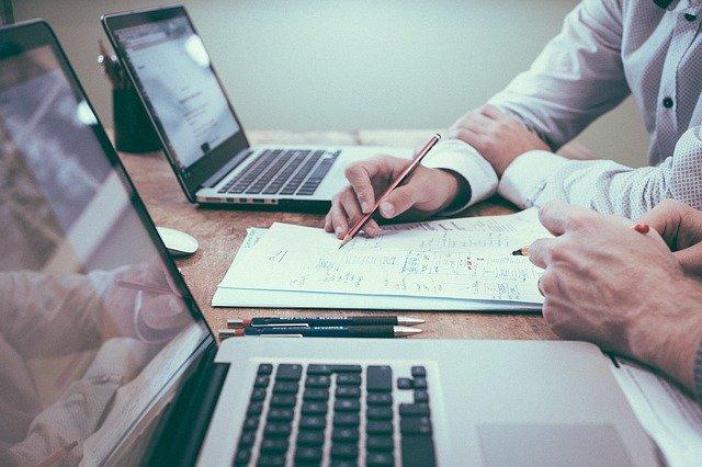 Muži pracujú pri stole v kancelárii